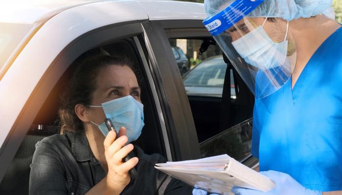 Patient and nurse at drive through Covid 19 testing centre// Image credit: iStock.com/Juanmonino