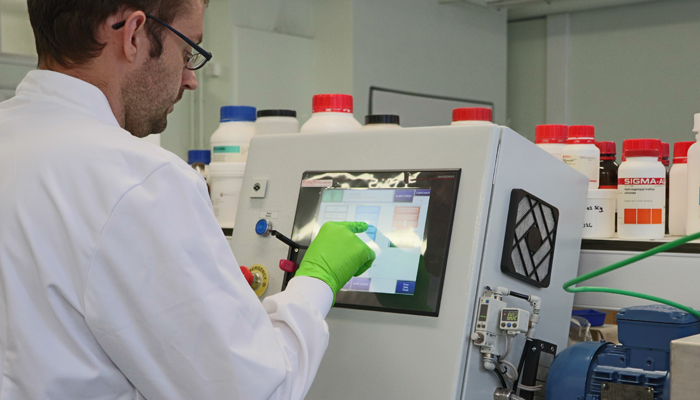 Operator using touchscreen control system on APT benchtop scale system