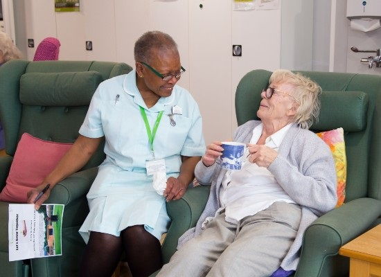 Barbara, a Healthcare Assistant at Arthur Rank Hospice Charity has a giggle with a patient receiving support from their Living Well Service.