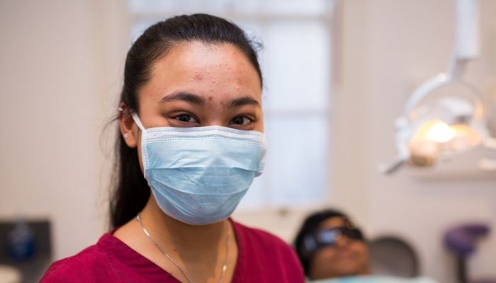 Dentist wearing mask with patient in background