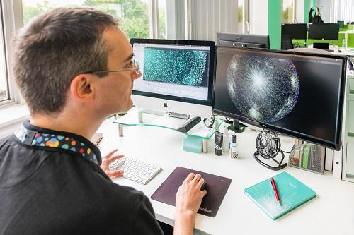 Healx_man sitting and looking at computer screens