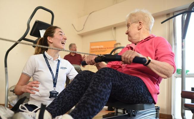 older woman on rowing machine with younger trainer