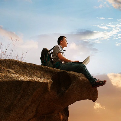 Man with laptop sitting on cliff edge and staring at the sky