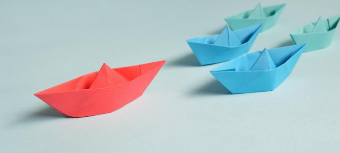 red paper boat leading two blue paper boats
