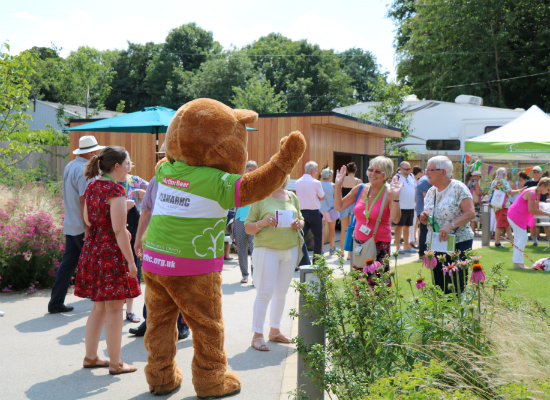 Bear greeting people in a garden