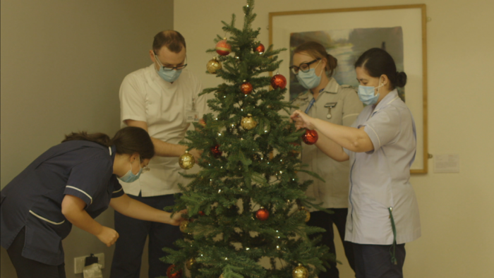 Staff decorate the Christmas tree - a still from Arthur Rank Hospice Charity's Light up a Life film premiere, which replaced the physical event this year.