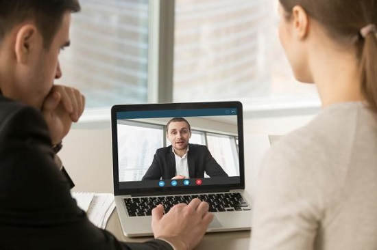 Two people in Zoom conversation with a man on the screen