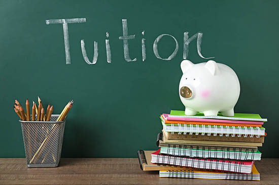 piggy bank and school books beside blackboard saying 'tuition'