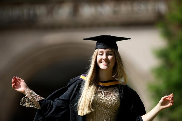 smiling girl graduate in gown and mortar board