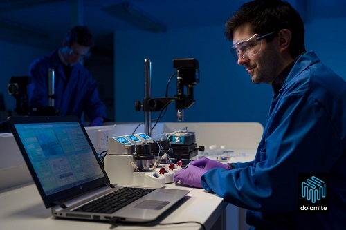 Researcher looking at microfluidics data on a laptop