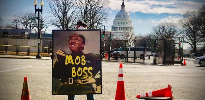 A protester holds a sign comparing President Trump to Italian dictator Benito Mussolini.  Credit: Maria Thalassinou via Unsplash