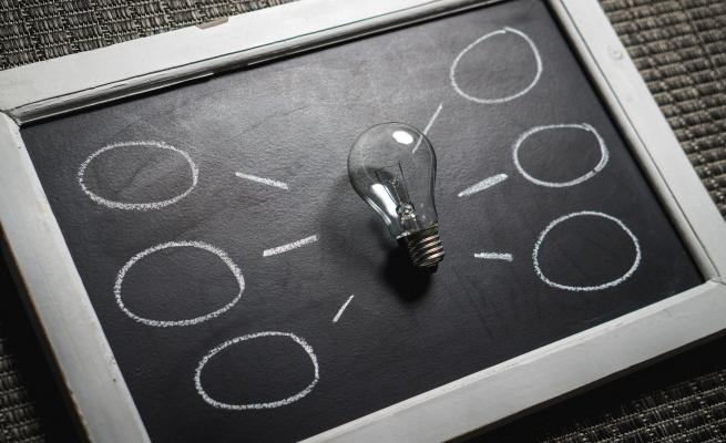 blackboard with a lightbulb on it  and empty thought bubbles