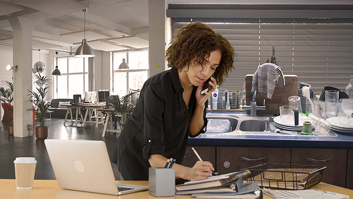 woman working from home with washing up in the background