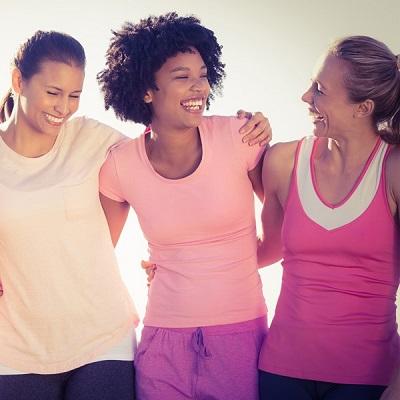 three smiling women hug each other