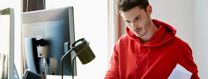 student looking at papers while sitting in front of computer