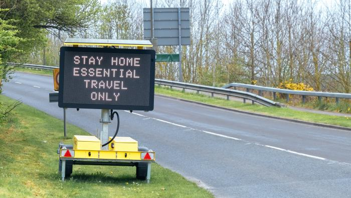 gantry in the road saying' stay home - essential travel only'