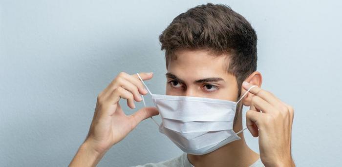 Man putting on a facemask  Credit: Kobby Mendez on Unsplash