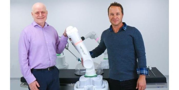 two men standing next to a surgical robot