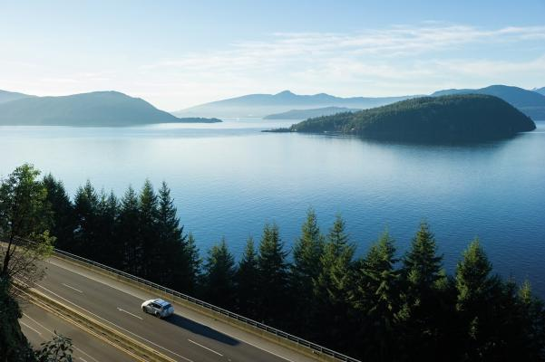 Car driving alongside a lake and forest